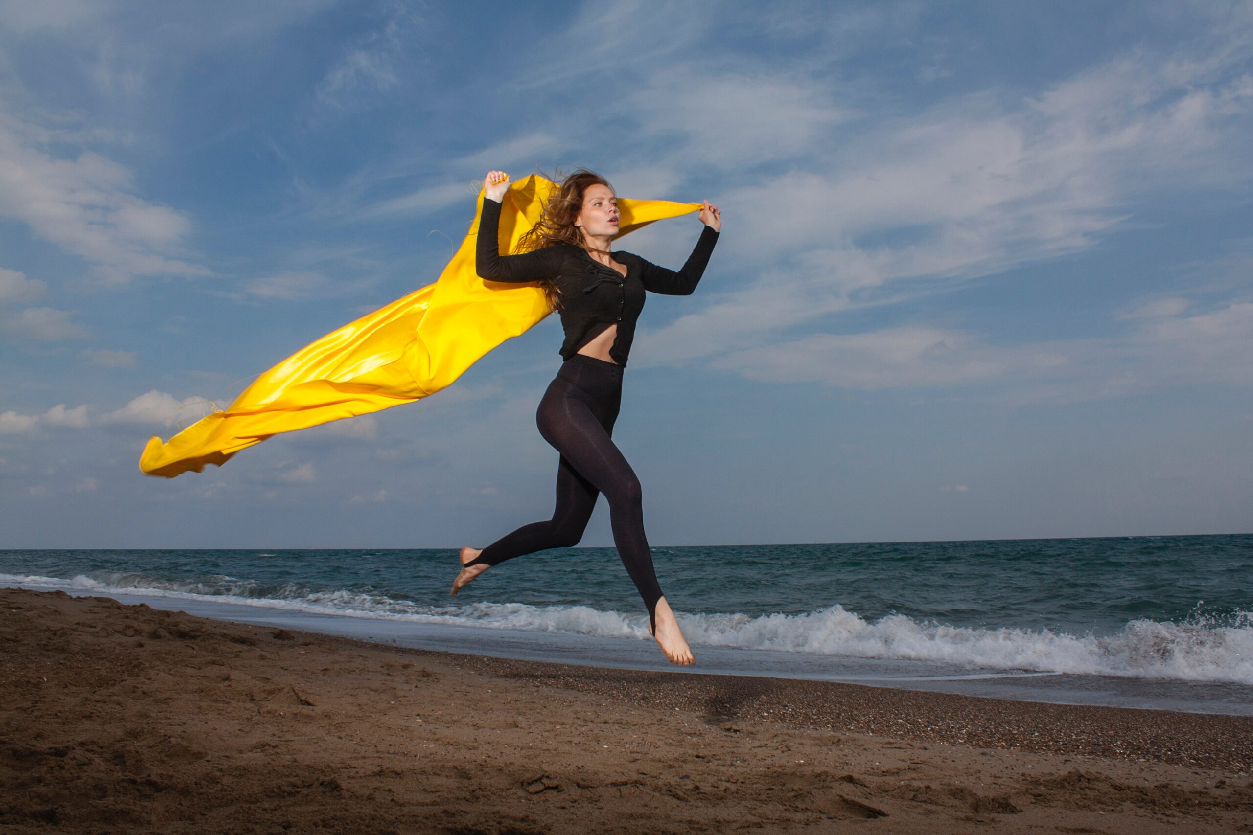 woman in yellow shirt and black leggings holding yellow textile on beach during daytime