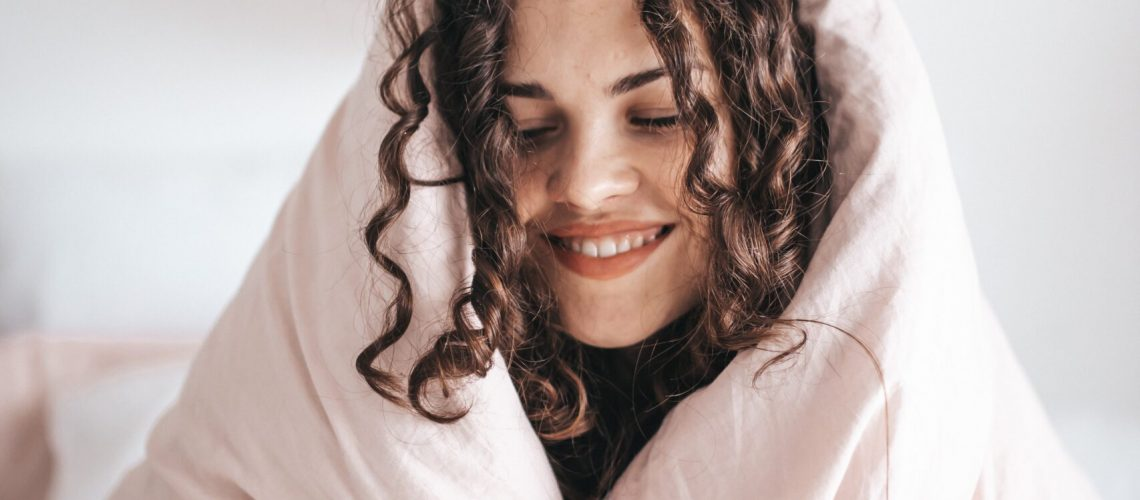 smiling woman wrapped in gray blanket